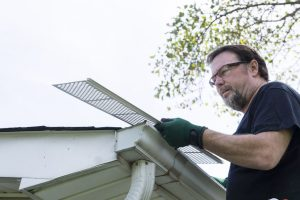 A Man Installing Gutter Guards On a Gutter System