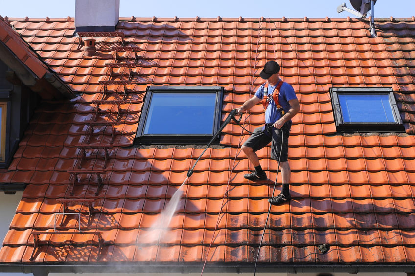 Professional Roofer Washing Roof With High Pressure Hose